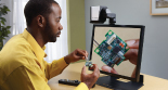 Photo: A man is using the SmartView 360 to work on a tiny object that looks like an electronic chip